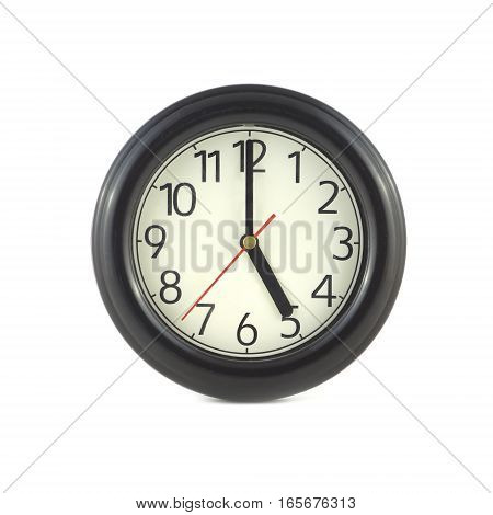 Big round wall clock, with a dark rim on a white background close-up and arrows showing five o'clock