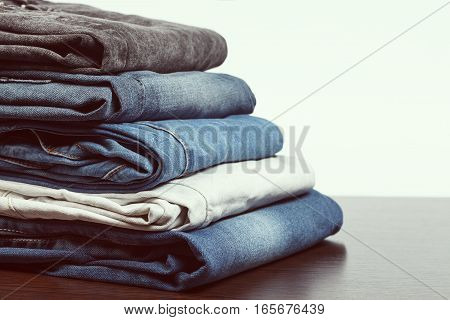 Stack of different aged folded jeans on wooden table. Low aperture shot focus on front part vintage tone