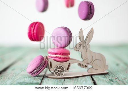 Colorful macaroon levitation with toy rabbit on wooden background. Easter concept