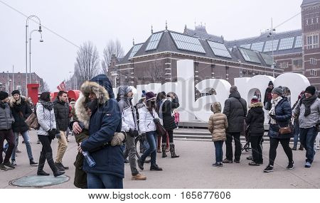 Amsterdam Netherlands- December 302016: Citizens hugging and taking pictures on the background of the letters of the city name
