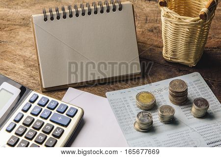 Blank notepad with calculator. Passbook blank paper and coins on wooden table for mocup display planning Money Financial Accounting Concept