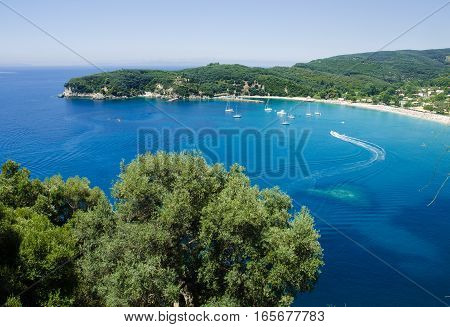 View from hill on boats on blue waters of Valtos bay and beach Parga Greece