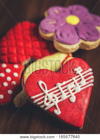 Close-up of several sugar cookies with royal icing glaze of different colors one red heart-shaped with musical notes in foreground