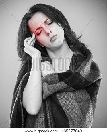 Young woman wrapped in blanket with her fingers to her temple as if experiencing headache grayscale portrait with red pain area