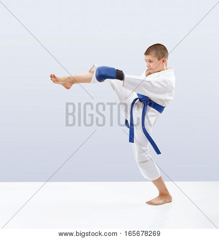 Boy with blue belt and overlays on the hands is beating kicking