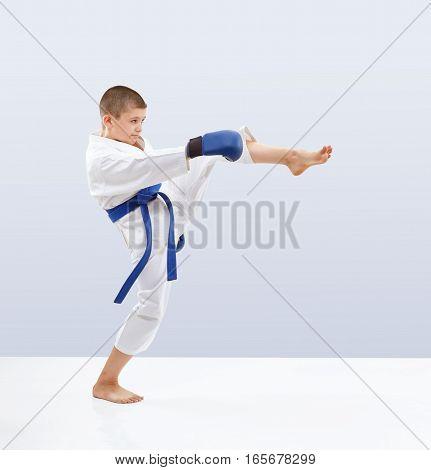 Little karateka is training kick leg forward