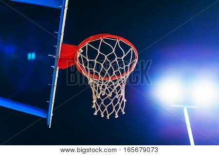 Basketball hoop on outdoor sport court at night with lens flare
