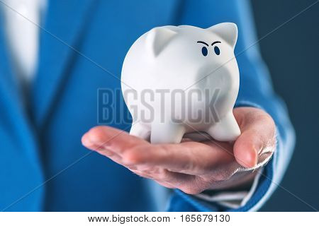 Angry piggy coin bank in businesswoman's hand selective focus