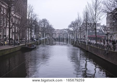 Amsterdam Nederland- December 302016: Along the canal walk citizens and moving vehicles