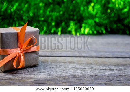 Box Gift Paper Wrapping On The Wooden Table. On A Background Of Green Tinsel