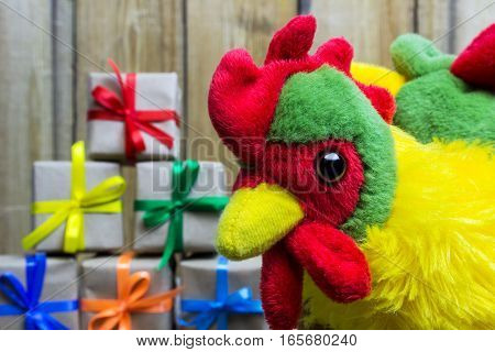 Rooster Stuffed Toy Looking Into The Lens, On The Background Of Gift Boxes. Symbol Of The Year