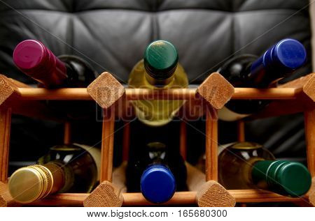 Wooden Wine Rack With Various Color Bottle Tops On Dark Background