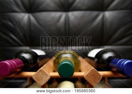 Closeup Of Bottles In A Wooden Wine Rack On Dark Background