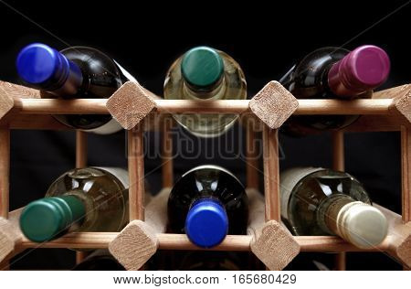 Wooden Wine Rack With Various Color Bottle Tops On Black Background