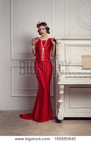Young Beautiful Girl In Red Dress Style Of The 20's Or 30's With Glass Of Martini Near The Piano. Vi