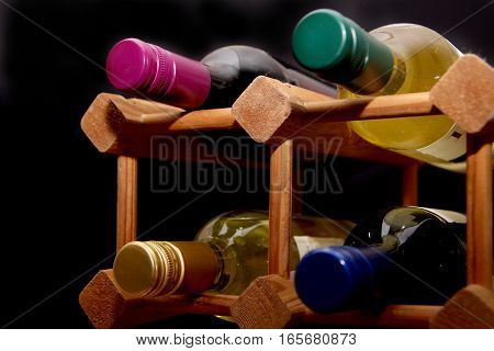 Different Colored Tops Of Wine Bottles In A Wooden Wine Rack On Black Background
