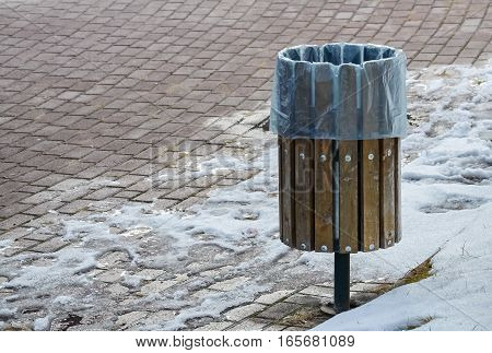 Metal trash can on the street in a cold winter day