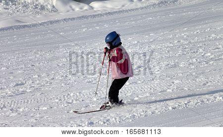 Little skier on ski at sun winter morning