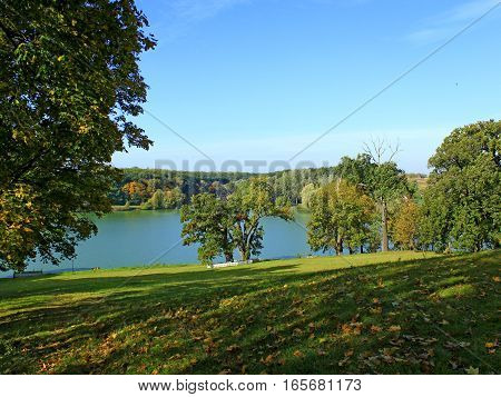 beautiful autumnal landscape with picturesque lake and trees