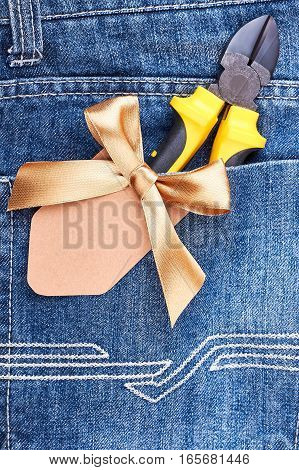 Pliers in blue jeans pocket. Pliers and ribbon bow. Surprise your man.