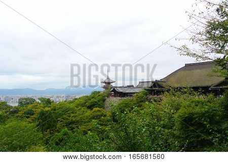 A view of Kiyomizu-Dera Temple from the outside with the city and mountains of Kyoto Japan in the background.