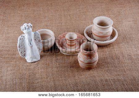 Composition of ceramic angel greybeards and candlestick with patterns on sackcloth background
