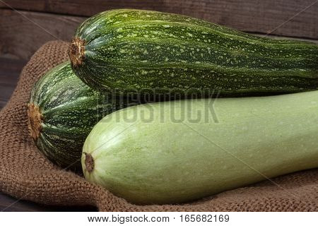 green zucchini and courgette on sackcloth and wooden background.