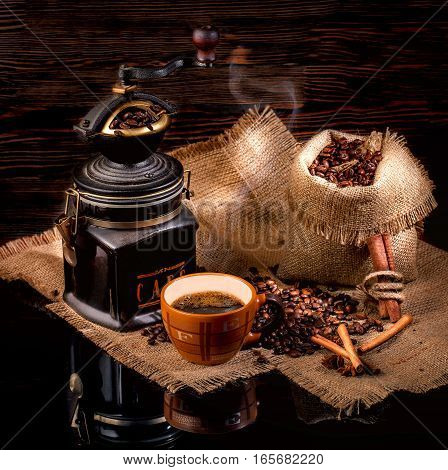 Cup of coffee, cinnamon sticks, star anise, a bag of roasted coffee beans on sackcloth stand on a glossy black surface, on a brown background
