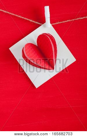 White Gift Card Wih Paper Hearts On Red Wooden Background.