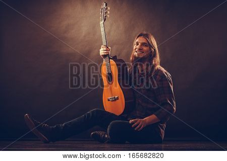 Music hobby concept. Happy young man with wooden guitar. Artist is sitting on the floor and exposing his instrument.
