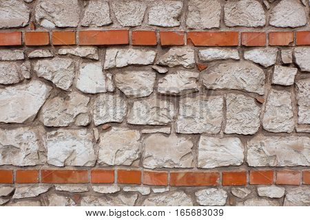 A stone wall made of white stone blocks that has two red brick horizontal lines. Found at an old castle / fortress. The picture of the wall is well usable as background pattern for titles or headlines or such.
