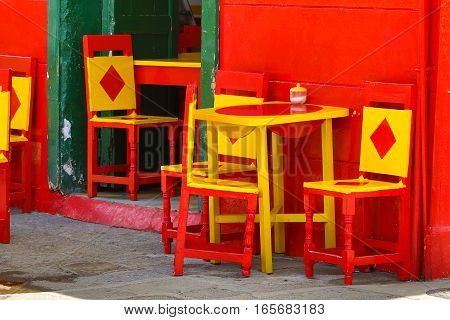 colourful chairs in front of a building in El Jardin Antioquia