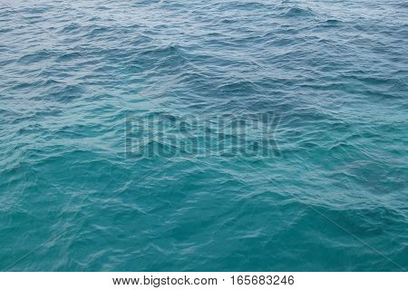 surface of the sea, close to a beach and lagoon at an island - the water is turquoise and blue colored and has light waves.