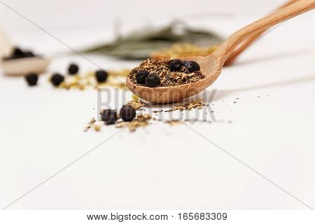 Many different medicinal herbs in wooden spoons on a white background isolated.