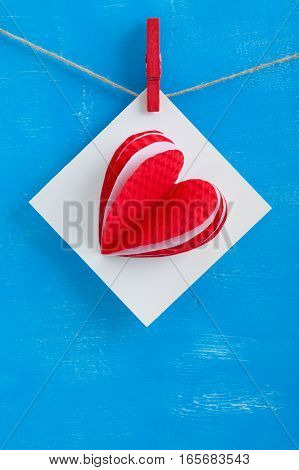 White Gift Card Wih Paper Hearts On Blue Wooden Background.