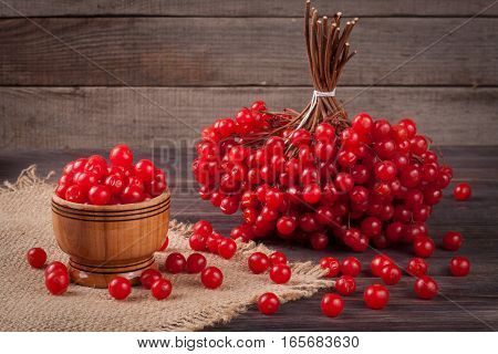 ripe red viburnum berries in a bowl on wooden background.