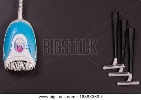 electric epilator with a razor on a dark background.