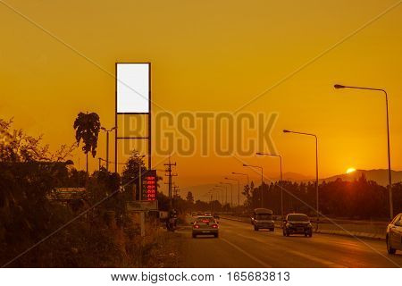 Blank billboard on Petrol station and Gas station at sunset with traffic rush on road.