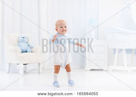 First steps of baby boy learning to walk in white sunny bedroom with bassinet rocking chair play mat and toy bear. Footwear for young children. Right shoes for little kids feet. Nursery interior.