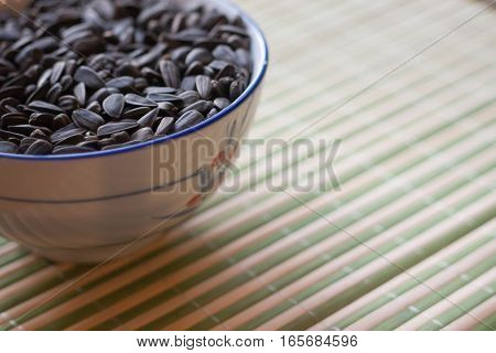 a bowl of sunflower seeds on a table with bamboo napkin.