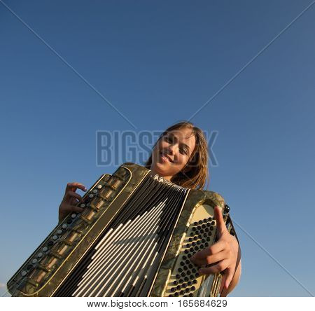 cute girl playing the accordion against a blue sky