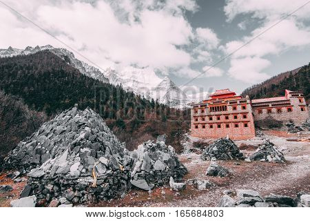 Tibetan temple on the snow mountain with gray rocks in Yading Nature Reserve, China. old tone