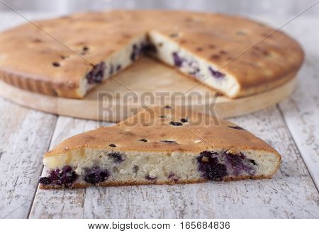 Pie with blueberries on a wooden tray.