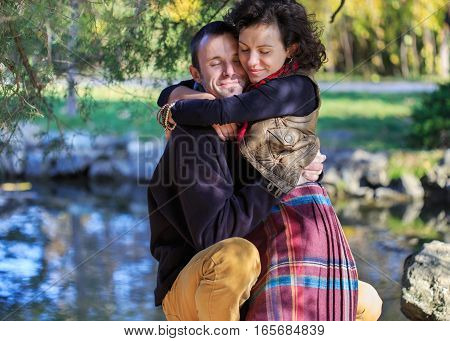 Loving couple in bright clothes hugging each other in the park near the lake