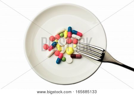Pills on white plate with fork. Pill instead of food. diet