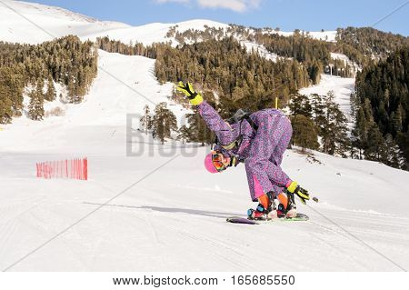 Beautiful beginner snowboarder girl in caucasian mountains
