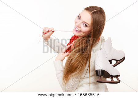Woman with ice skates getting ready for ice skating winter sport activity. Smiling girl wearing warm clothing on white studio shot