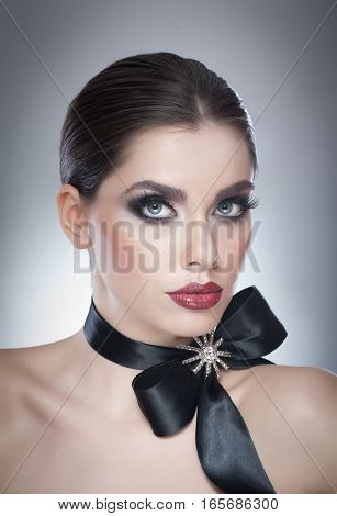 Hairstyle and Make up - beautiful female art portrait with black ribbon. Elegance. Genuine Natural brunette with ribbon - studio shot. Portrait of a attractive woman with beautiful eyes and red lips