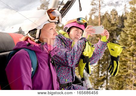 women snowboarders photographed on the phone while sitting in the lift cabin