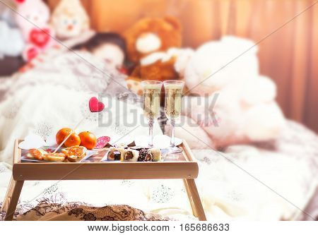 Healthy breakfast in bed with champagne. Sleeping woman in bed. Valentine's Day romantic concept